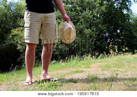 Man in shorts with a hat is standing in the backyard