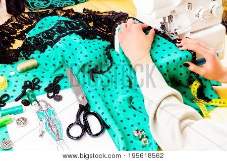 Workplace of a dressmaker: buttons spools scissors sketch buckle fabric lace and beads. Girl sewing dress with the help of sewing machine