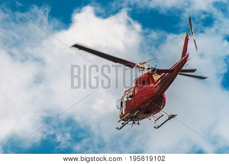 Red Helicopter Logging in the Air. Heli-Logging Transportation.