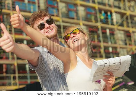 Real estate and family concept - young couple on front of new big modern house with blueprint project dreaming about home showing thumb up sign
