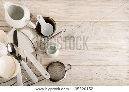 Kitchen tools of white and steel color (accessories) for baking on a light wooden background. Selective focus.