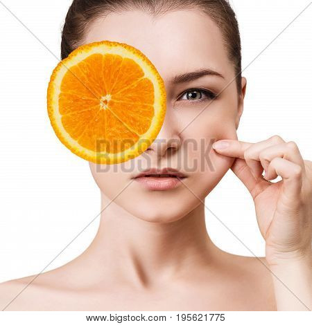 Woman covering eye by orange slice and pulling cheek. Elasticity skin concept.