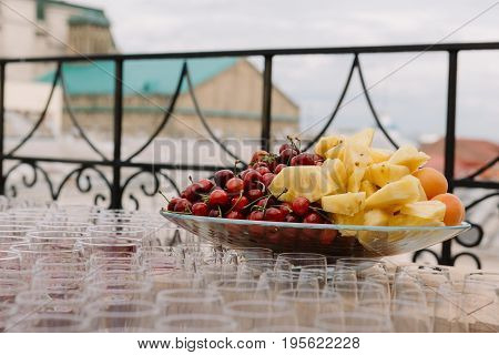 Fruit plate with cherries, pineapples, apricots for the wedding catering on the bocals