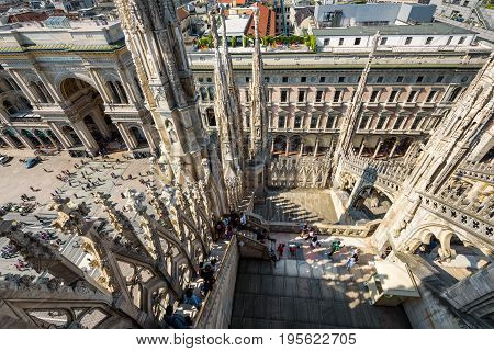 Milan, Italy - May 16, 2017: Tourists visit the roof of the Milan Cathedral (Duomo di Milano). View of the Piazza del Duomo with the Galleria Vittorio Emanuele II from the top of the Milan Duomo.