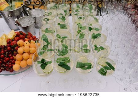 Lime and mint drink in bocals next to the fruit plate for the wedding catering