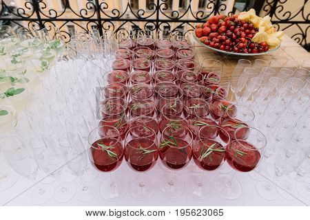 Red beverage in the wineglasses decorated with rosemary leaves for the wedding catering