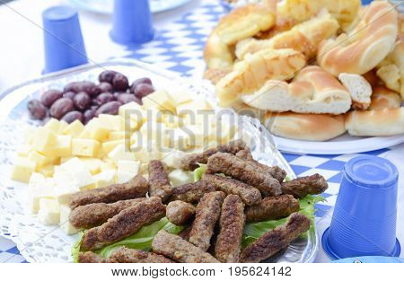 Traditional Balkans kebaps and slices of chees on a platter image of a poster