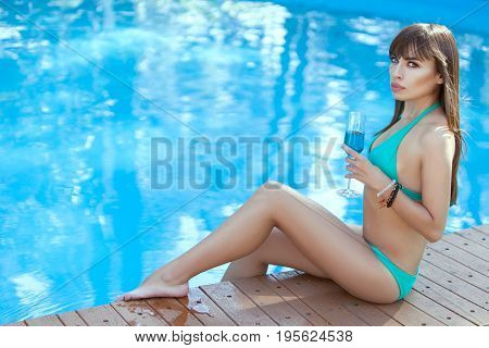 Woman is sitting on the edge of the pool with a glass of wine in her hand.