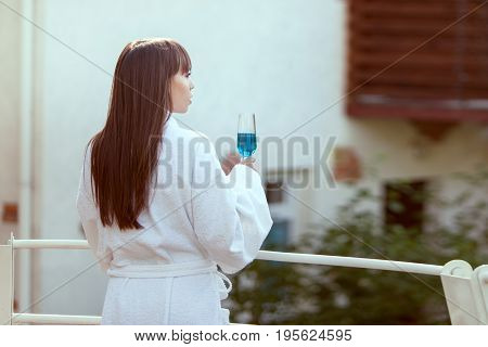 Woman is resting on the veranda with a glass of wine in her hand.