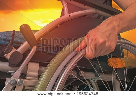 Handicapped Disabled Man Sitting On Wheelchair Outdoors At Sunse