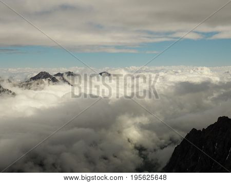 Rugged snow covered mountains rising up above thick clouds at sunrise