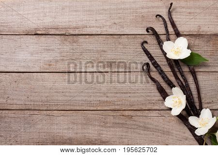 Vanilla sticks with flower and leaf on a old wooden background with copy space for your text. Top view.