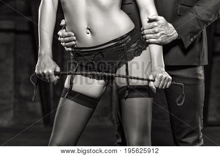 Sexy dominant woman in underwear with whip seducing rich man closeup black and white