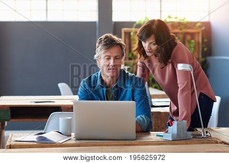 Two trendy dressed young business partners using a laptop and talking together, while standing at a table in a modern office with sun flare