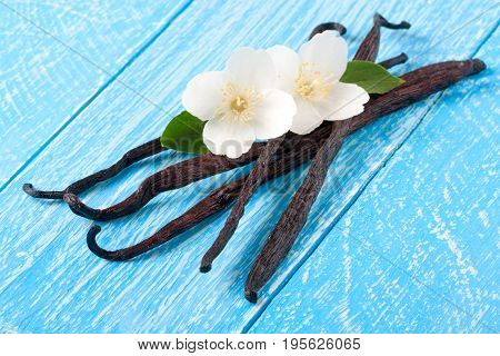 Vanilla sticks with flower and leaf on a blue wooden background.