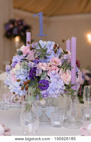 Wedding table decoration with the the violet, blue, pink flowers, greenery and candles