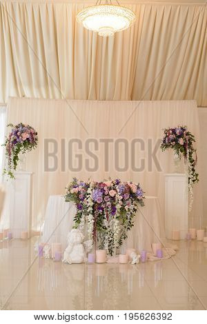 Wedding table decoration in ivory and lilac colors with the flowers and initials of the fiance and fiancee as the coat of arms