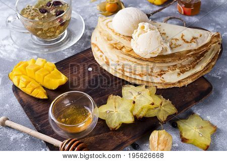 Pancakes with mango Ice Cream, mango, carambolla and honey on stone background, flat lay