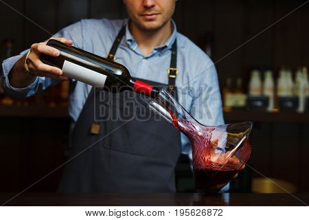 Sommelier pouring wine into glass from decanter. Male waiter on background of bar counter with bottle of red wine