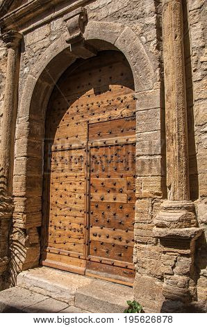 Wooden door and stone arch in ancient Châteaudouble church, a quiet and tourist village with medieval origin on a sunny summer day. Located in the Var department, Provence region, southeastern France