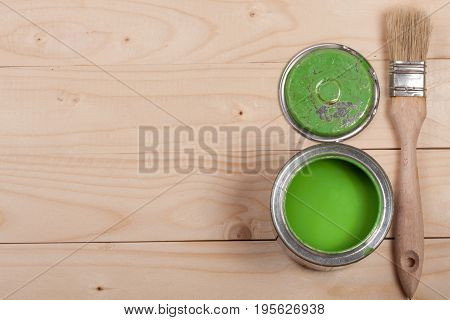 green paint in the bank to repair and paint brush on the light wooden background with copy space for your text. Top view.