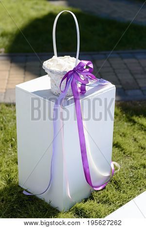 Wedding white basket decorated with violet ribbon on the pedestal