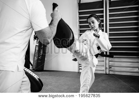 Taekwondo instructor working with little girl on training indoors black and white image