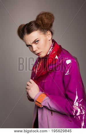 Young model with hairdo posing in coat and pink plastic fabric in studio.