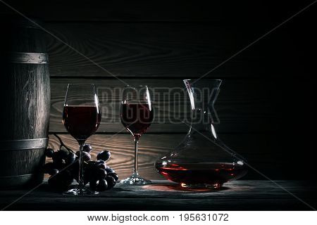 Decanter, two glasses of red wine and wooden barrel on a wooden table