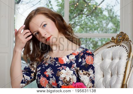 A beautiful young girl in a bright colorful dress sits in a chair near the window and adjusts her hair. Beautiful blue eyes and bright makeup. Interested and playful look.