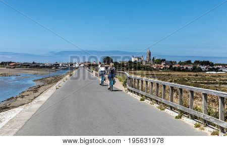 two women cycling on the Jacobsen Jetty on the island of Noirmoutier (France)