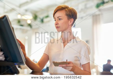 Bistro worker registrating new order by cash-register