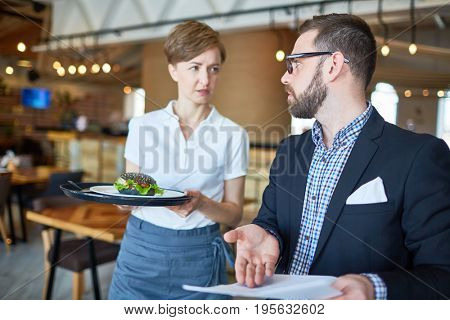 Waitress with sandwich serving businessman in cafe