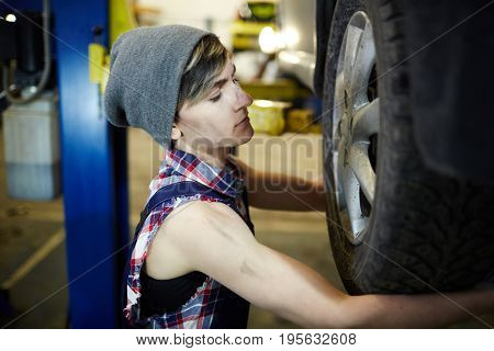 Professional mechanic fixing car tire or wheel