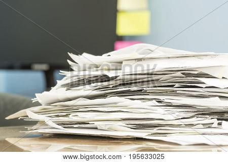 stack of documents on desktop in office.