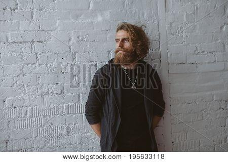 Bearded blonde man wearing hoodie locket black shirt standing against while brick wall looking away.