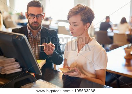 Owner of cafe and servant discussing new order on cash register display