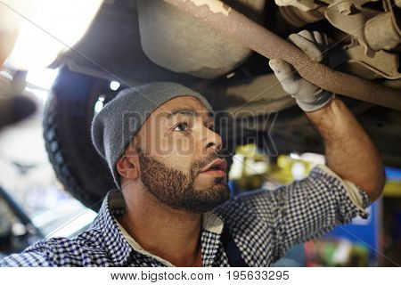 Young engineer checking car parts in garage