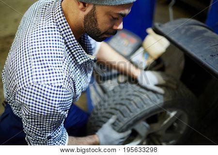 Professional car mechanic with wheel overhauling vehicle