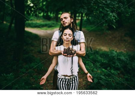 A man and a woman in the forest with their eyes closed holding bumps