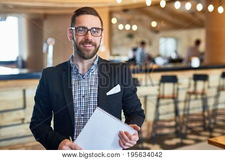 Businessman with notepad looking at camera in restaurant