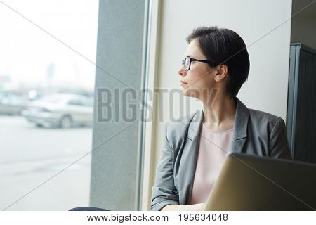 Pensive salesperson looking through office window