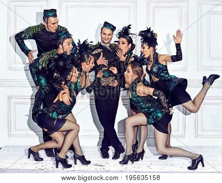 The studio shot of group of dancers posing at retro costumes. Concept of cabaret, luxury party and jazz