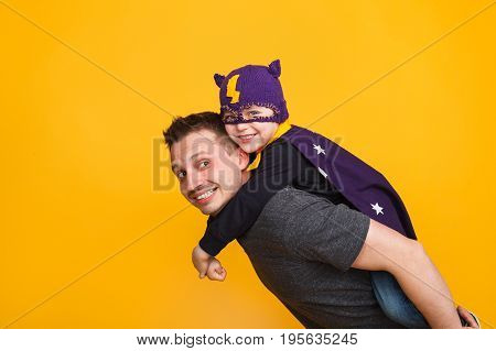 Side view of man holding little son in superhero costume on back and posing on orange backgorund.