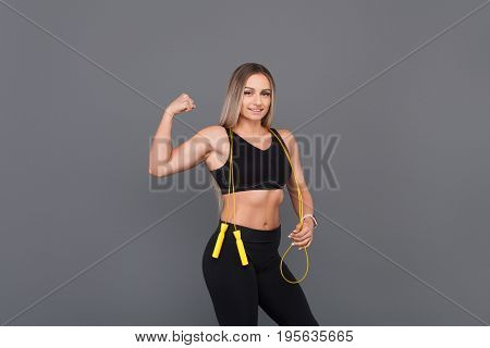 Beefy blonde woman wearing black sportswear flexing muscles holding jumping rope.