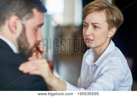 Businesswoman putting hand on shoulder of colleague and comforting him