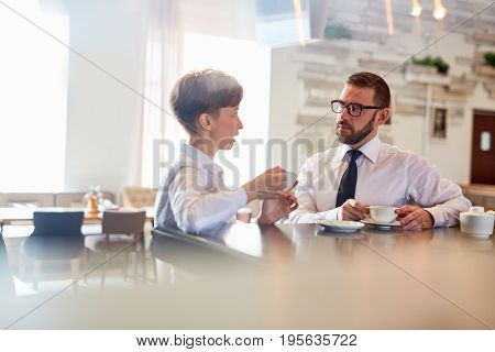 Two entrepreneurs having dialogue about joint business in cafe