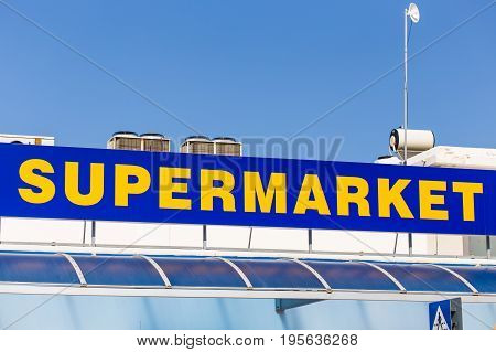 Supermarket sign on building. Yellow and blue inscription supermarket