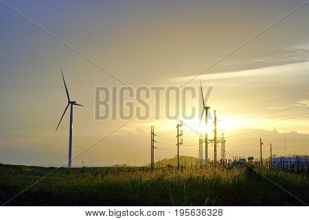 Wind turbine farm with power line and power plant during beautiful sunset Alternative green energy for protection of nature at Khao Kho Phetchabun province Thailand