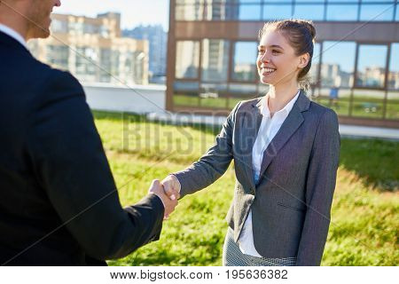 Successful partners greeting one another by handshake